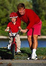 Picture of a father teaching his young son how to ride a bicycle