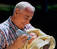 Picture of a grandfather holding his newborn grandson, feeding him a bottle