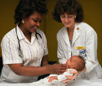 Picture of a newborn being examined by two nurses