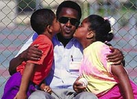Picture of two young children kissing their father on the cheek