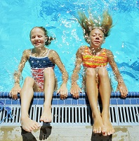 Photo of two girls with their heads in the water at poolside