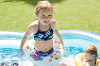 Photo of young girl standing in inflatable pool