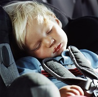 Photo of young boy asleep in car seat