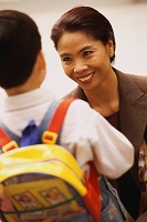 Photo of woman in business attire smiling at her young son with his backpack