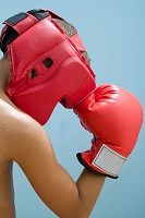 Photo of young teen holding boxing glove to boxing helmet