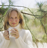 Photo of woman holding mug of coffee in front of tree