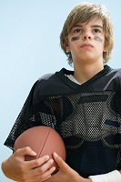 Photo of teen boy in uniform, holding football