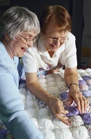 Photo of two women quilting