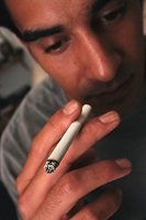 Photo of man with burning cigarette