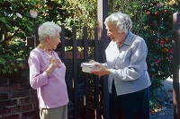 Photo of older woman giving casserole to another woman