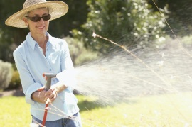Older woman wearing wide-brimmed hat and long sleeve shirt while watering in the yard