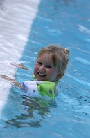 Photo of young girl with water wings in pool