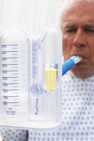 Photo of older man using a spirometer