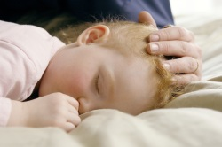 Photo of sleeping toddler, parent storking its head.