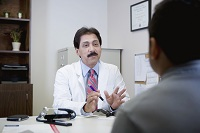Photo of doctor talking with patient in office