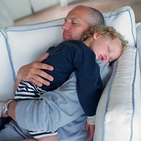Photo of youngster and dad asleep on the couch