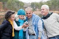 Photo of four people outdoors, taking a picture