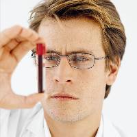 Photo of lab worker looking a vial of blood