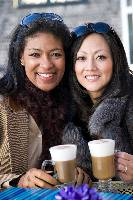 Photo of two women drinking coffee beverage