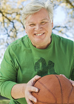 Mature man holding a basketball and smiling