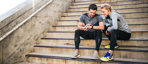 Man and woman looking at watch during workout
