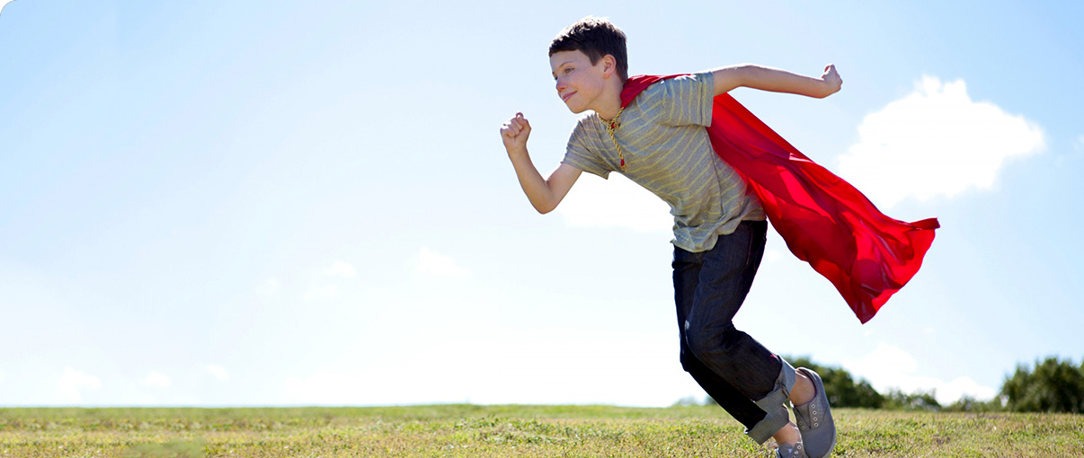 Boy with superhero cape running