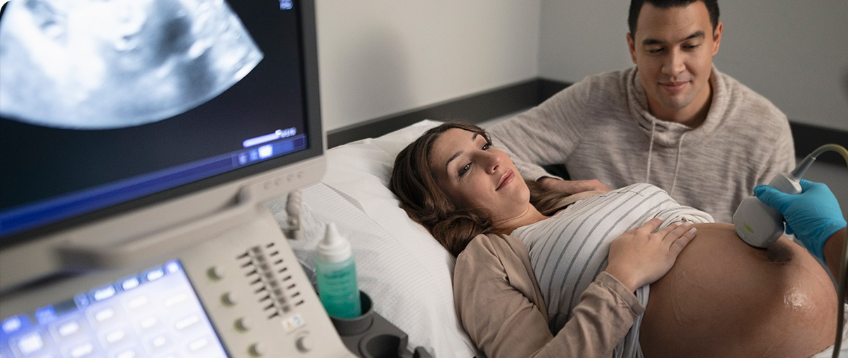 Man and pregnant woman holding hands while viewing ultrasound