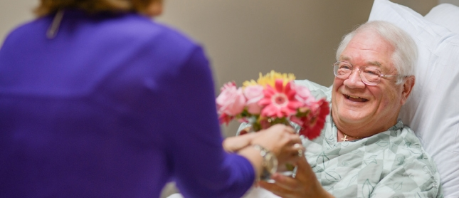 patient in bed receiving flowers from a volunteer
