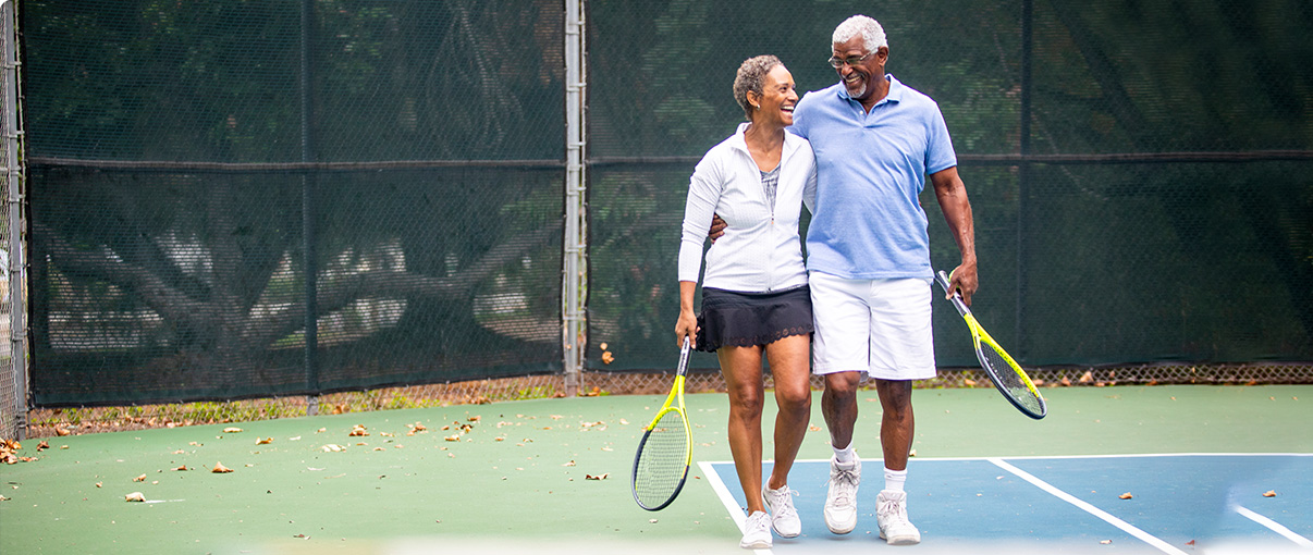 Man and woman walking and laughing on tennis court