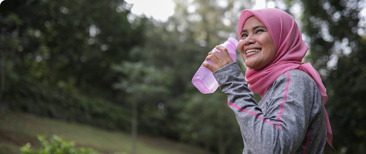 Woman drinking water after jogging in park
