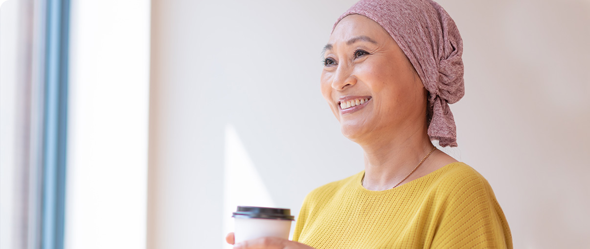 Female cancer patient smiling while holding coffee cup