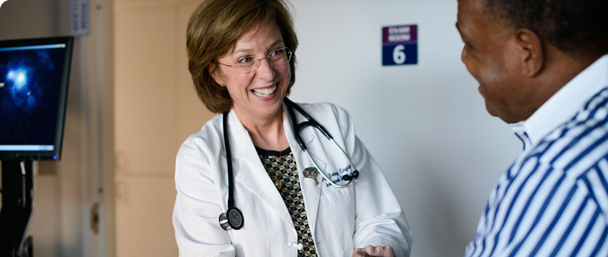 Female doctor smiling while talking with male patient