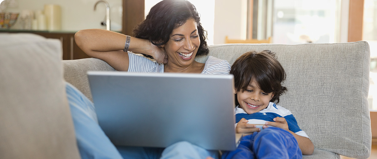 Mother and little boy laughing on couch with laptop