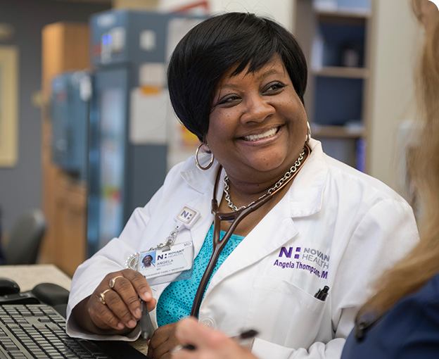 Female African American doctor smiling at nurse while sitting at computer