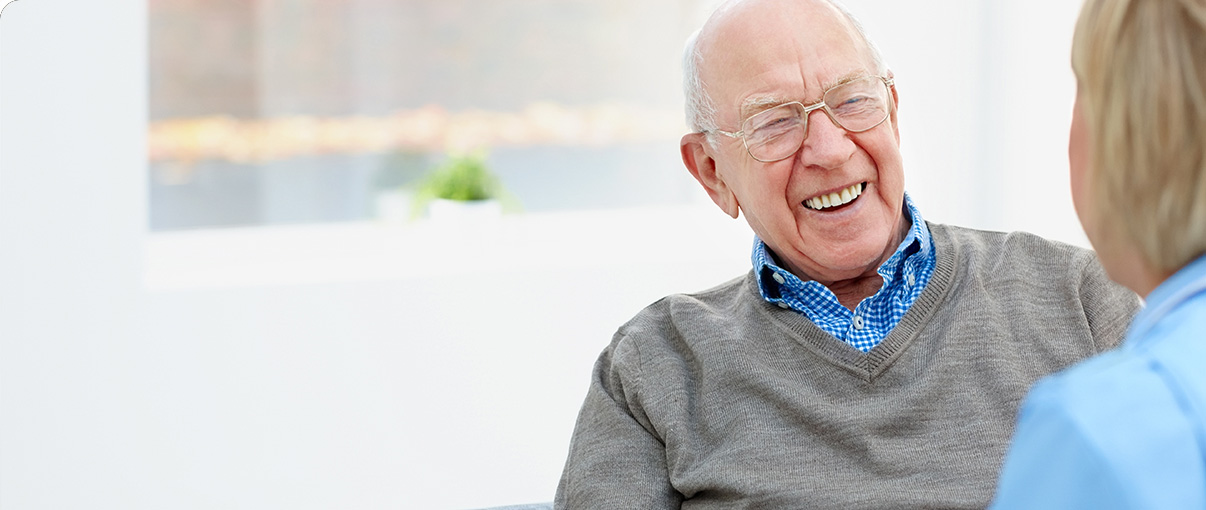 Older man smiling at nurse