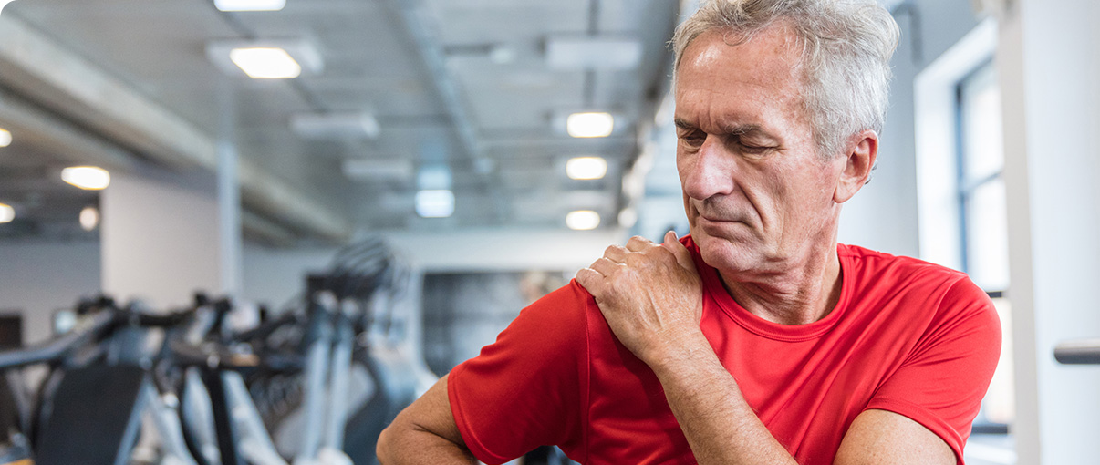 Older man rubbing shoulder in gym while working out