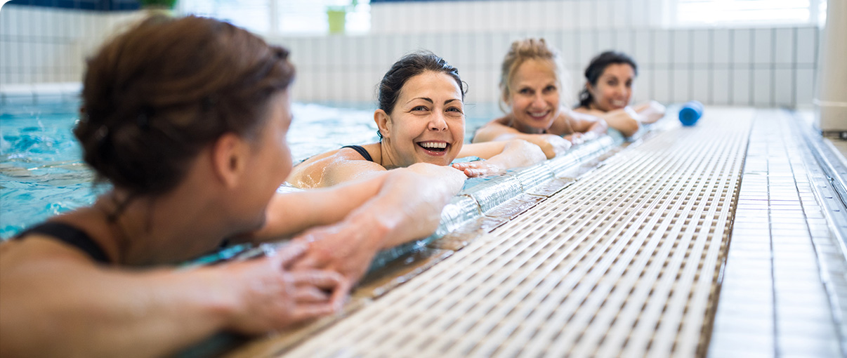 Women smiling while swimming in pool