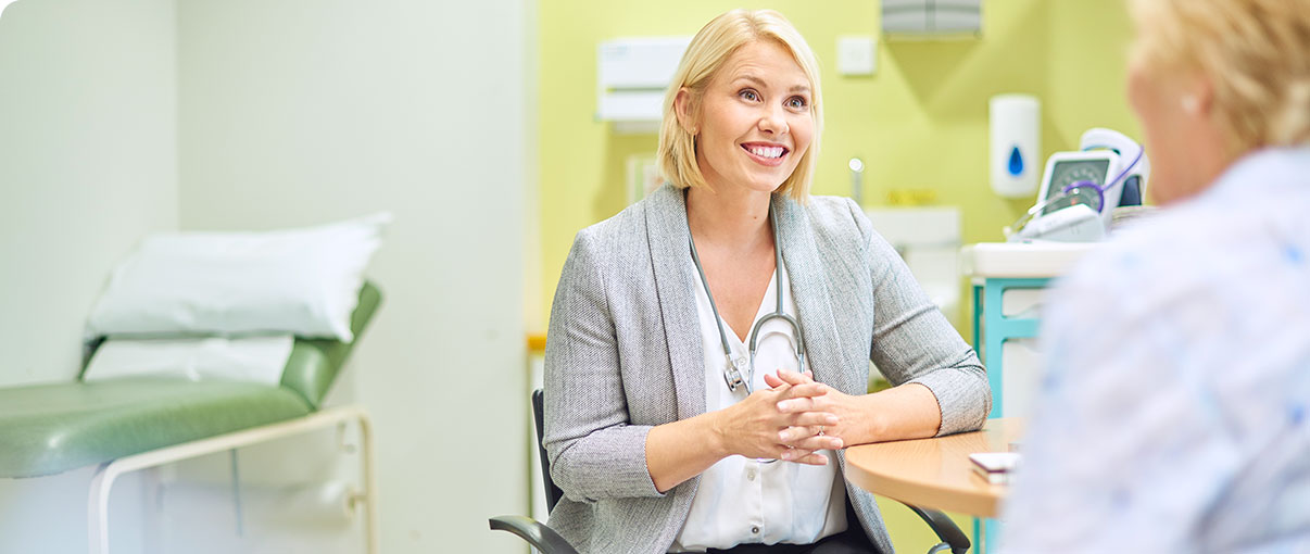 Female doctor smiling at patient in exam room