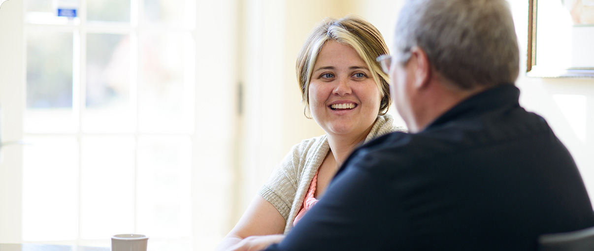 Woman smiling while talking with weight loss counselor