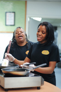 two African American women singing while they work